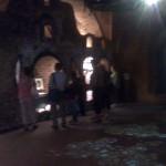 Vieni turistai pro griuvėsių angas žiūri sugriautų trakų paveikslus, kiti šoka ant grindų, griaudami akmenis