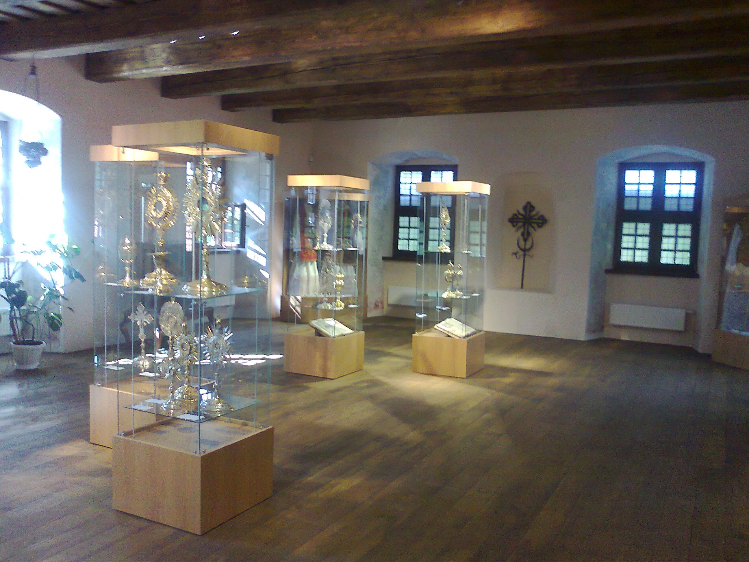 Bendras salės vaizdas - medinės grindys, medinės lubos, kuklūs baldai ir neįkainojami eksponatai