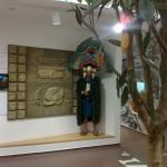 Indėnas ir plastikinis medis neužgožia gražaus meno kūrinio ant sienos